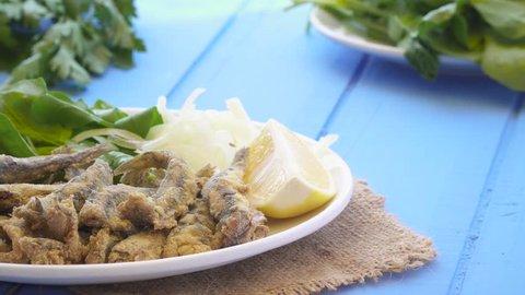 Turkish Hamsi Tava with lemon and arugula. Fried Anchovies close up view.