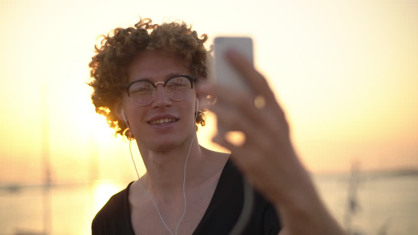 Happy young caucasian male having friendly video call during sea sunset, pointing at background. Yellow lights. Slow motion