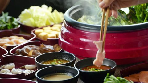 enjoy eating Shabu Shabu and Sukiyaki in hot pot at japanese  restaurant.Japanese food are high quality food cooking in hot boil soup with vegetable beef raw meat or sea food hold with chopsticks