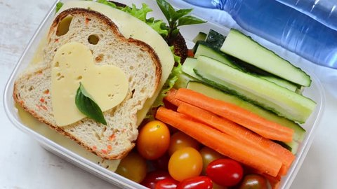 Healthy lunch box with sandwich and fresh vegetables, bottle of water.