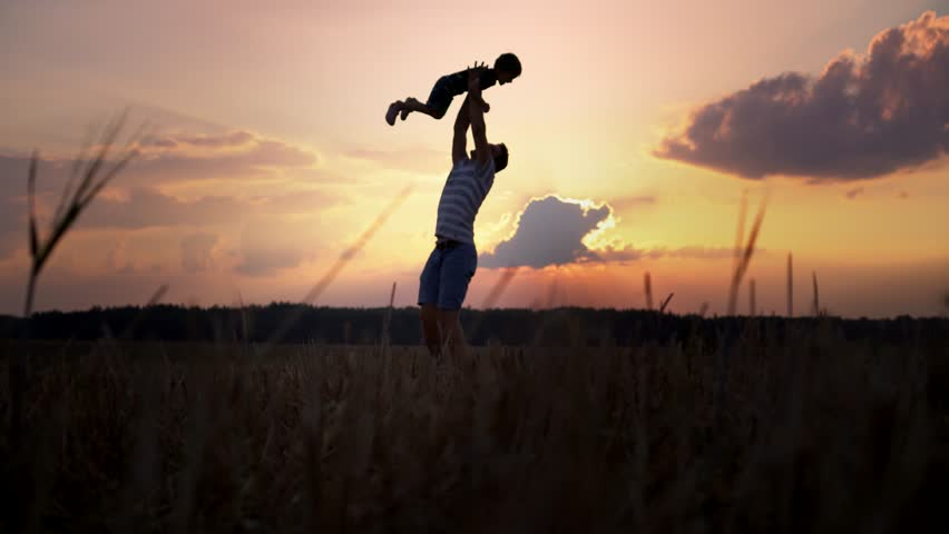 Father and son run to the sunset. The father raises the child in his arms and throws up #31096300