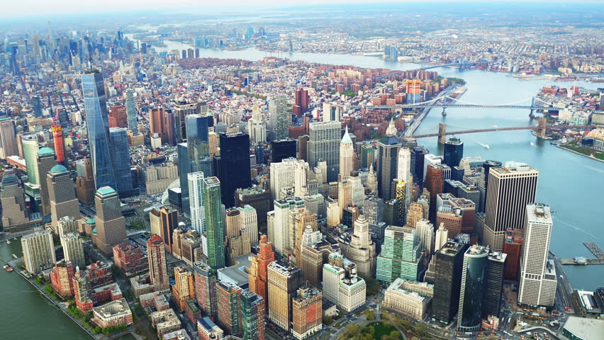 Aerial view of skyscrapers in Lower Manhattan. Brooklyn and Manhattan Bridge in the background. Shot from a helicopter.