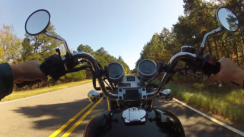 A wide angle shot of the point of view of someone riding a motorcycle on a