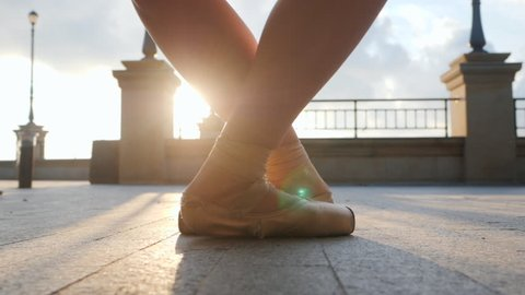Close up of a ballet dancer's feet as she practices pointe exercises on the stone embankment. Woman's feet in pointe shoes. Ballerina shows classic ballet pas. Slow motion. Flare, gimbal shot