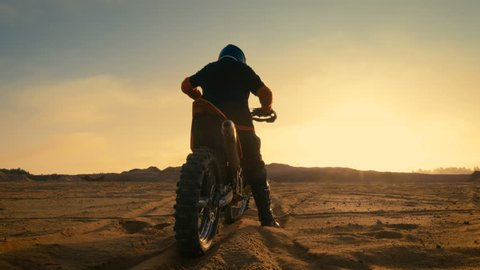 Following Shot of the Professional Motocross Driver Riding on His FMX Motorcycle on the Extreme Off-Road Terrain Track. Shot on RED EPIC-W 8K Helium Cinema Camera.