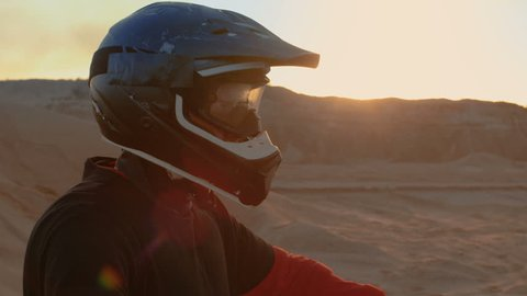 Close-up Portrait Shot Of the Extreme Motocross Rider in a Cool Protective Helmet Standing on the Off-Road Terrain He's About to Overcome. Background is Sandy Track. Shot on RED EPIC-W 8K Camera.