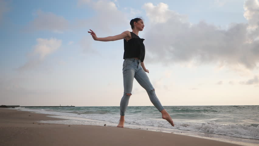 Young woman in casual style - denim and black top doing ballet at the beach. Attractive ballerina practices in jumping on sandy coastline in autumn. Slow motion.