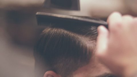 Male hairdressing with comb. Drying hair man. Close up of male hair style. Hairdresser blowing hair man. Hairstyle man in salon. Combing hair with dryer