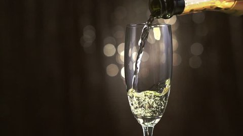 Champagne. One Flute with Sparkling Wine. Pouring Champagne over golden Holiday Bokeh Blinking Background. Celebrating. Glass of champagne close up. Slow motion 4K UHD video