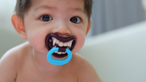 asian kid baby sucking nipple pacifier fancy vampire teeth dracula monster in halloween celebration party