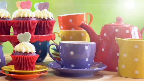 Colorful Mad Hatter style tea party with cupcakes and rainbow colored polka dot cups and saucers, with bokeh garden background and lens flare, panning up close up.