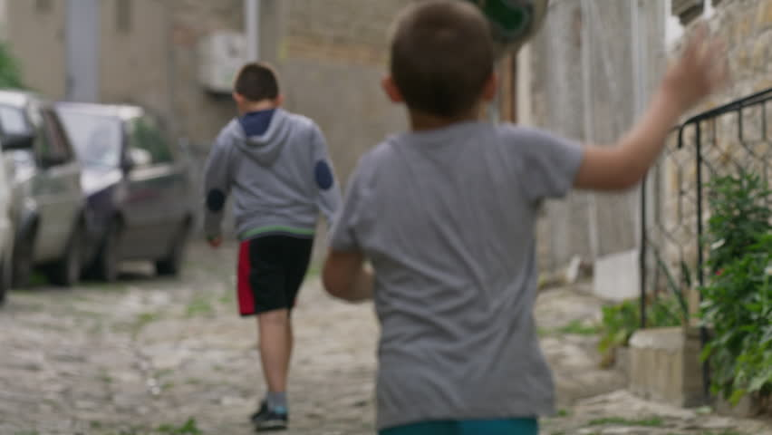 Medium slow motion panning shot of children playing street soccer / Veliko Tarnovo, Bulgaria
