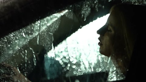 Sad, tired driver sitting in the car in the rain. Slow motion. Close up. Rain drops falling on the car.