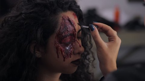 Make-up artist make the girl halloween make upin studio.Halloween face art.Woman applies on professional greasepaint on the face of spanish girl.War-paint with blood, scars and wounds.Slow motion.