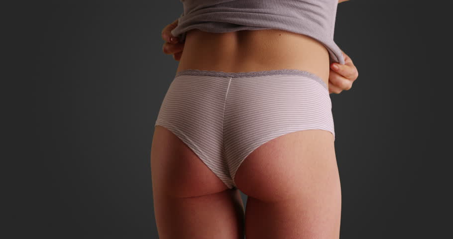 f09f0ddde29 Close up of Caucasian woman in striped panties lifting up tank top on solid  grey background. Rear view of slender female in her underwear lifting up  shirt ...