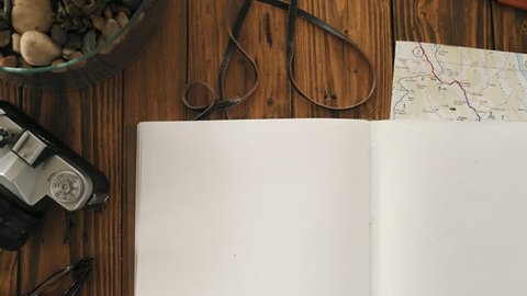 Close up top view on rustic wooden table and big a4 notebook with pure white recycled paper sheets turning over and over. Loop video of page turning of personal diary