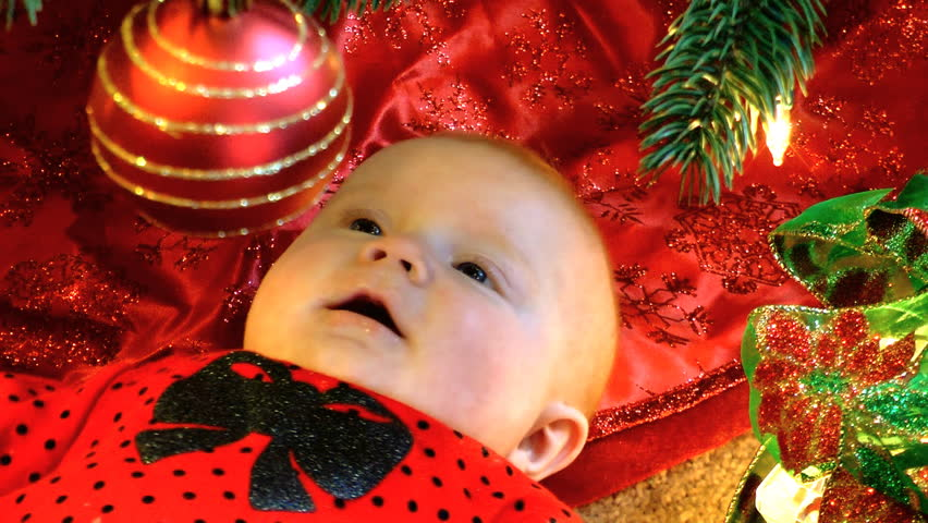 A Happy Baby Underneath A Christmas Tree Is Fascinated By The ...