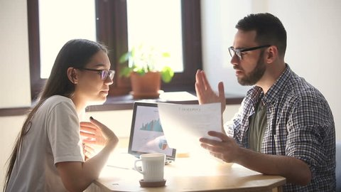 Man and woman arguing disagreeing about bad business contract, colleagues having conflict dispute about document sitting at office desk, partners shouting breaking agreement with unacceptable terms