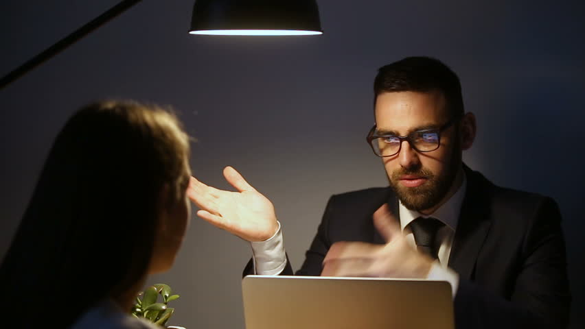 Successful businessman in suit glasses consulting talking to woman sitting with laptop at desk late under lamp light, company executive discussing explaining problem to employee at meeting overtime
