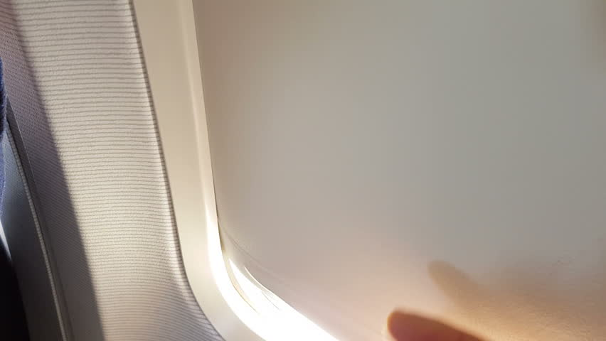 Passenger point of view man in flight raises aircraft window shade from an airplane seat and looks out on the wing. Sunny day and clear sky.   Shutterstock HD Video #31316860