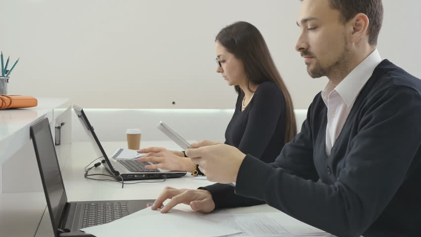 Business people works in the office, man uses tablet, woman works on laptop | Shutterstock HD Video #31330540