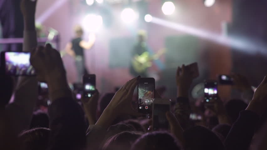 Slowmotion shot of a concert. People shoot videos on their cell phones. Rock concert.