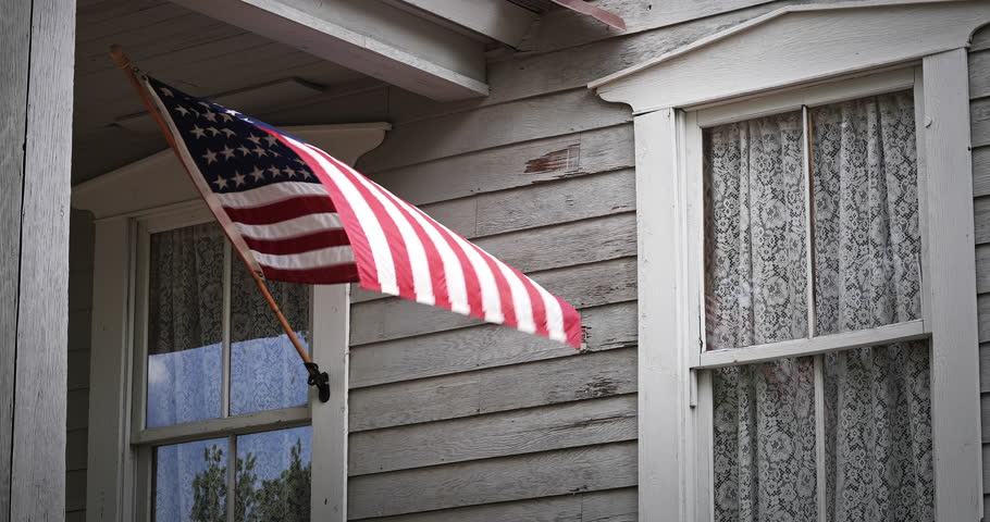 An American flag gently waves on a Victorian house front porch.