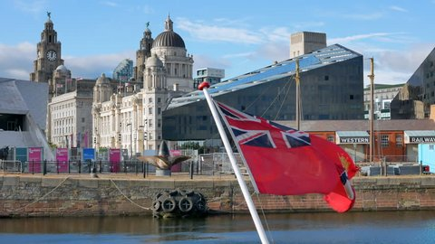 LIVERPOOL, NORTH WEST ENGLAND / UNITED KINGDOM - AUGUST 28, 2017: The Three Graces seen across Canning Dock with the Great Western Railways building and the flag at the foreground in Liverpool, UK.