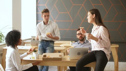 Business team of young people enjoying eating pizza together, millennials group talking having fun sharing lunch in cozy office, good relationships at work, food delivery service and catering