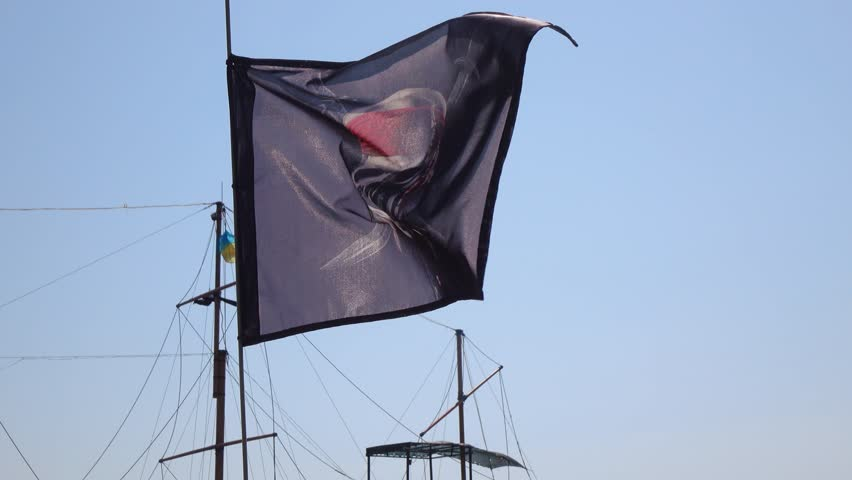 Against the backdrop of a sailing ship flags a pirate flag #31352410
