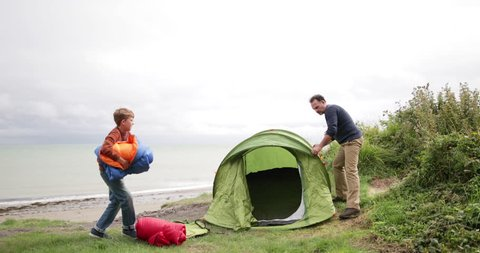 Father and Son putting up a tent together