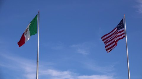 CIRCA 2010s - U.S.-Mexico border - The Mexican flag flies beside the American flag along the US border in Tijuana.