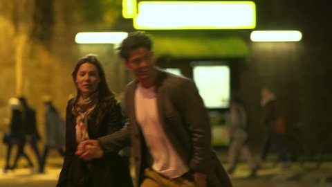 A man and a woman are holding hands as they walk across a busy London street at night. They dodge between cars in order to cross the road and many pedestrians are walking in all directions.