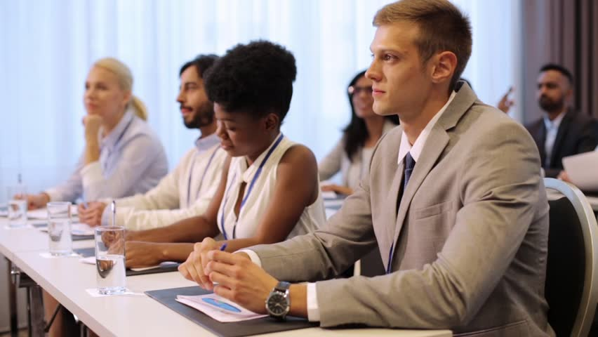 Business and education concept - group of people listening and taking notes at international conference | Shutterstock HD Video #31415110