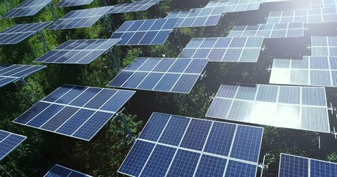 4K Aerial view of Solar Panels Farm (solar cell) with sunlight.Drone flight fly over solar panels field renewable green alternative energy concept in Thailand.