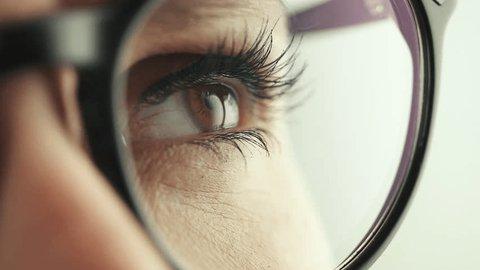 Thoughtful Female eye with glasses, slow motion