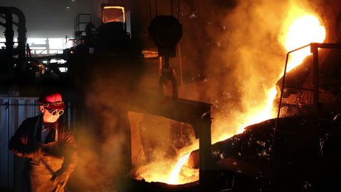 Hard work In foundry, melting iron, steel mill. Workers controlling iron smelting in furnaces, too hot and smoky working environment