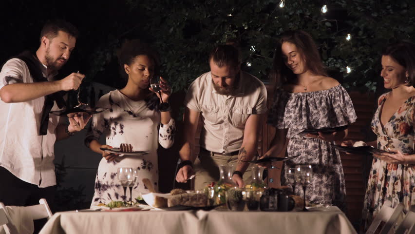Cheerful Group Of Friends Slicing Cake And Partying Together In Garden At Night