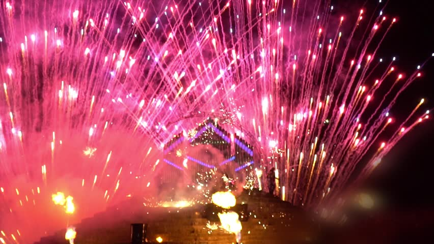 Fire show near the fire organ surrounded by pink salutes, slow motion