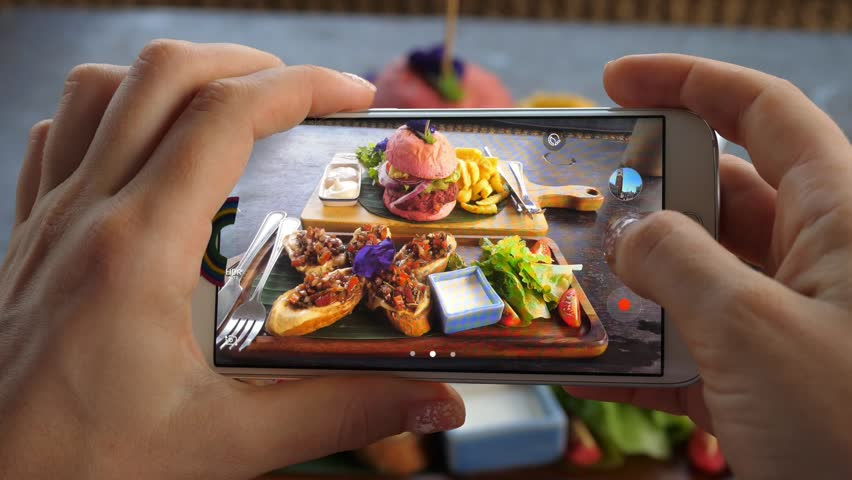 Female Hand Taking Pictures With Smartphone Of Food: Burger With Fries. Closeup.