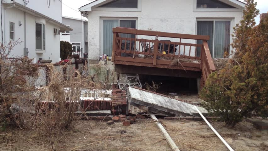 BREEZY POINT, QUEENS, NY-December 2, 2012: Footage clip of damaged home from waves and storm surge due to Hurricane Sandy. Video tilts up to reveal debris on deck that was uplifted from ocean water.