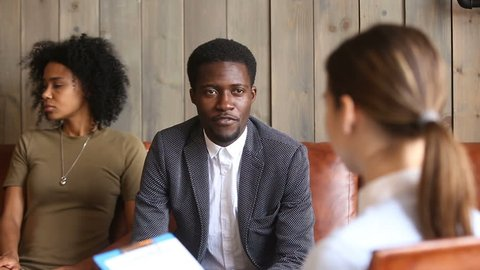 African man talking to family counselor, black unhappy couple at psychologists office, frustrated husband sharing marital problems while offended wife sitting silent on couch, marriage counseling