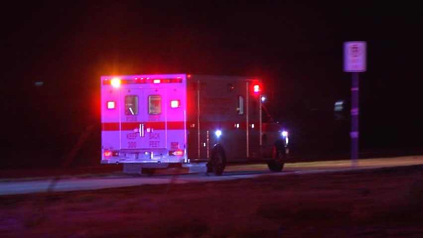 Ambulance drives down long road at night with flashing lights