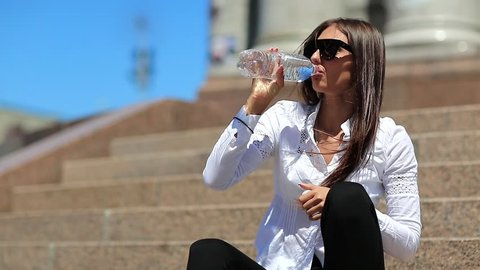 Young woman sits on the stairs and drinks mineral water from bottle. Beautiful girl with long hair in sunglasses drinks clean water. Girl opens plastic bottle of water and drinks soda water