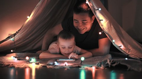 Father and son play and watching smartphone in children's room in tent with Christmas decorations