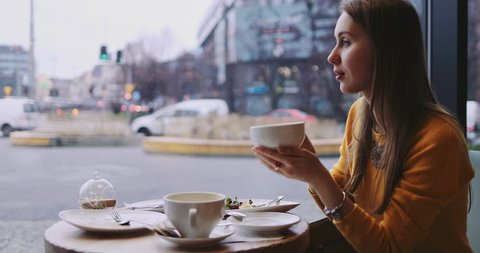 Woman Drinking Coffee in a Cafe. Busy City Traffic Behind the Window. SLOW MOTION 4K DCi. Girl enjoying hot beverage on a cold rainy day, sitting by the window table in the coffeeshop.