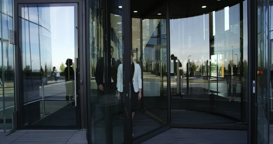 4k00 09two Business People Leaving Building Through Spinning Door And Talking
