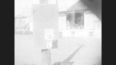1930s: sign for US 10 S in Montana stands near building on road as woman in hat walks. entrance to Yellowstone trail garage with AAA logo attached to structure on main street of town.