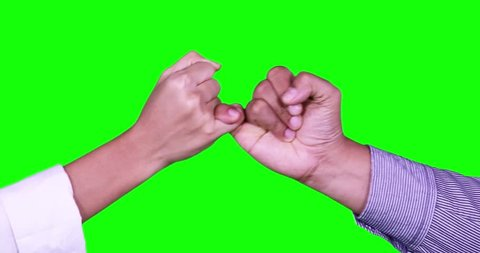 Two hands making a pinkie promise in front of green screen background. Shot in 4k resolution