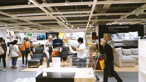 PARIS, FRANCE - CIRCA 2017: IKEA furniture store and seniors adults with children customers browsing through modern  decoration warehouse goods choosing the rights objects for their new home